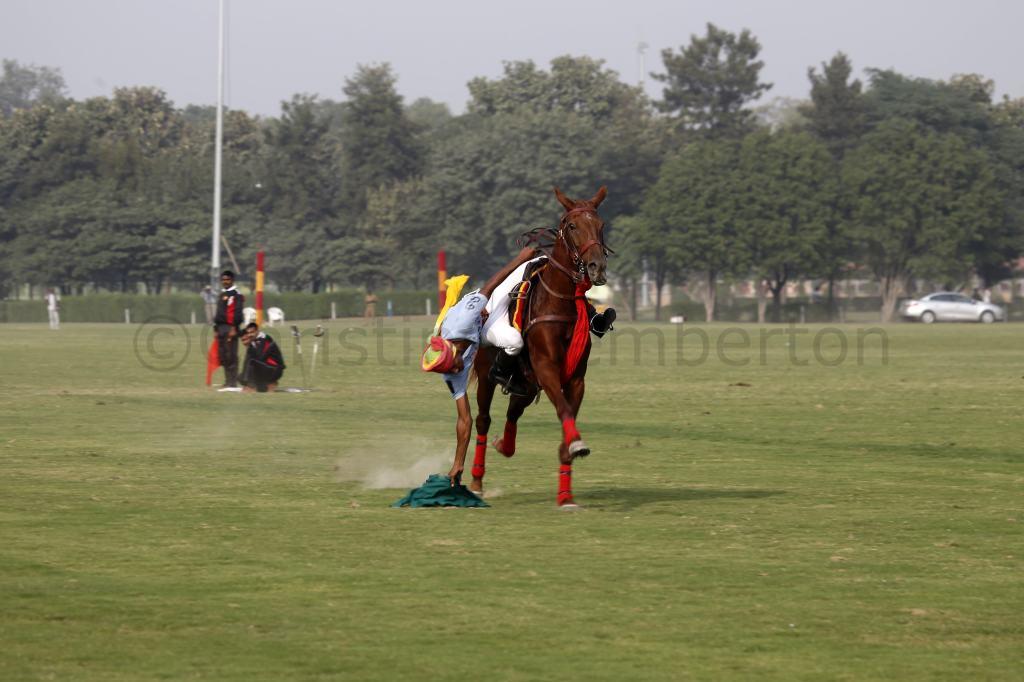 India. New Delhi. Display of trick riding. Hanky picking.
